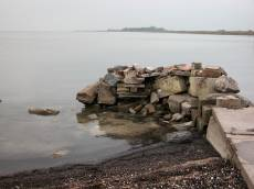broken pottery dike seafront stones pile heap