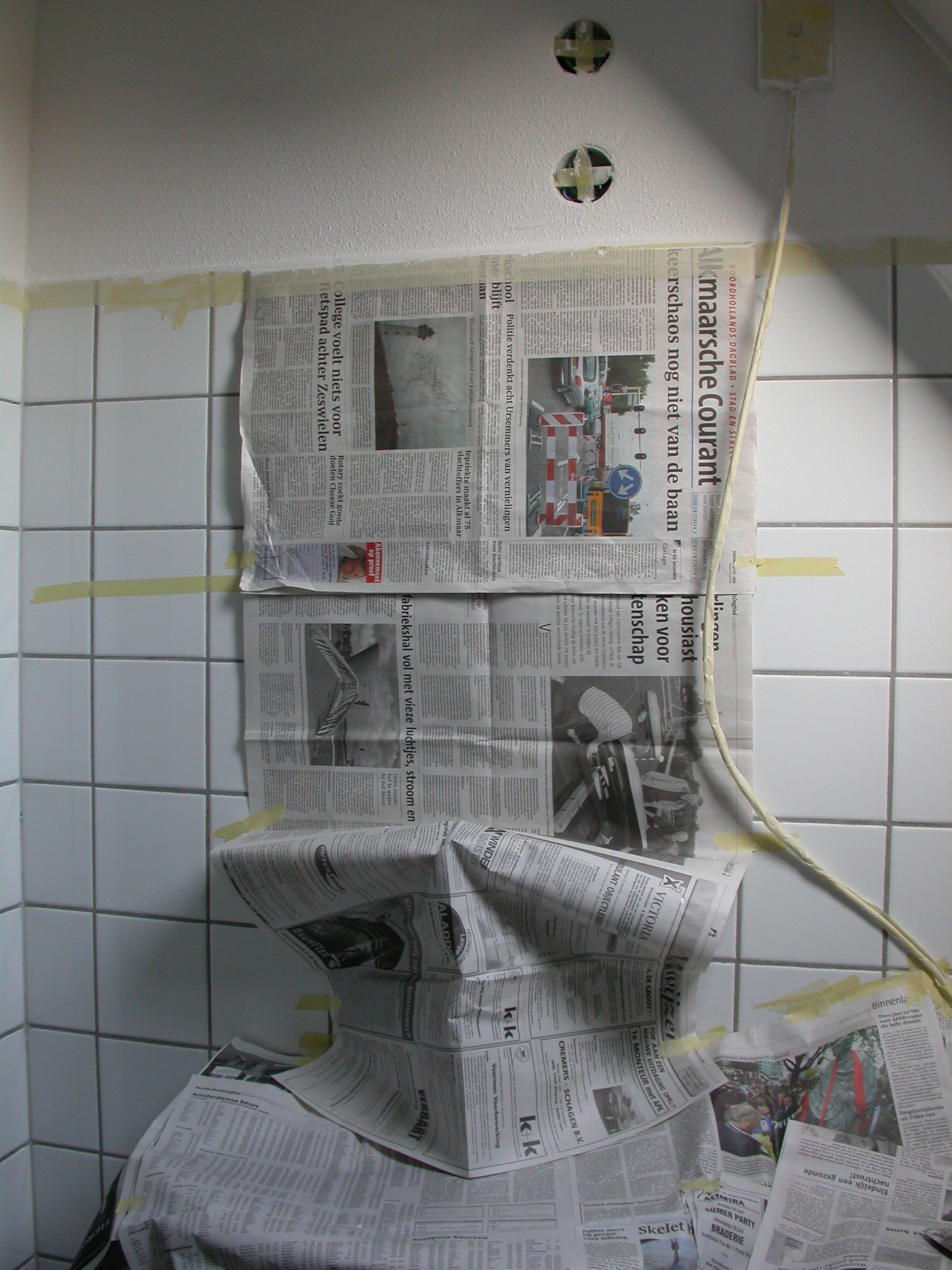 paul sink covered with newspapers taped to a bathroom wall