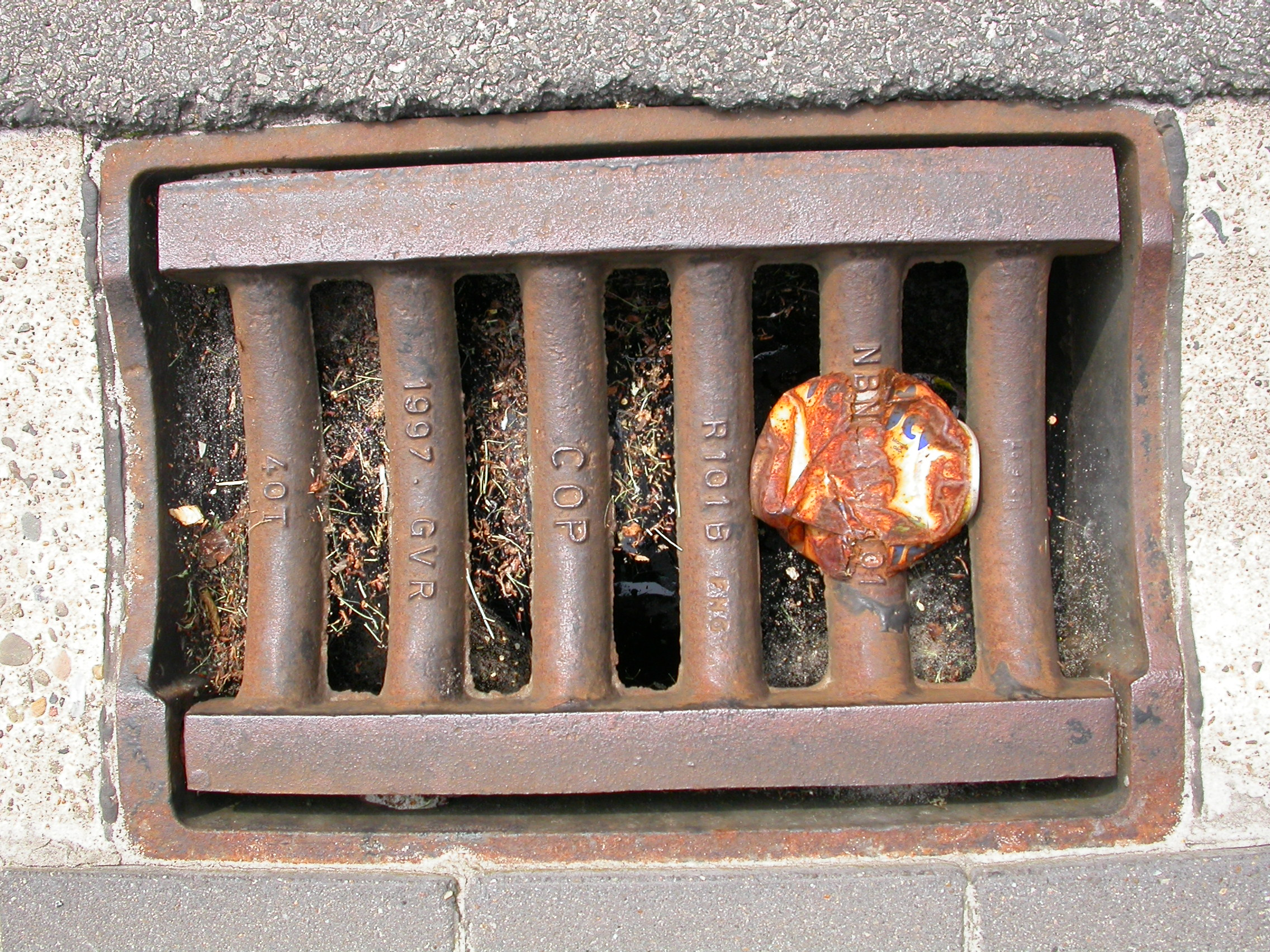 paul sewer lid metal bars garbage squashed fanta can