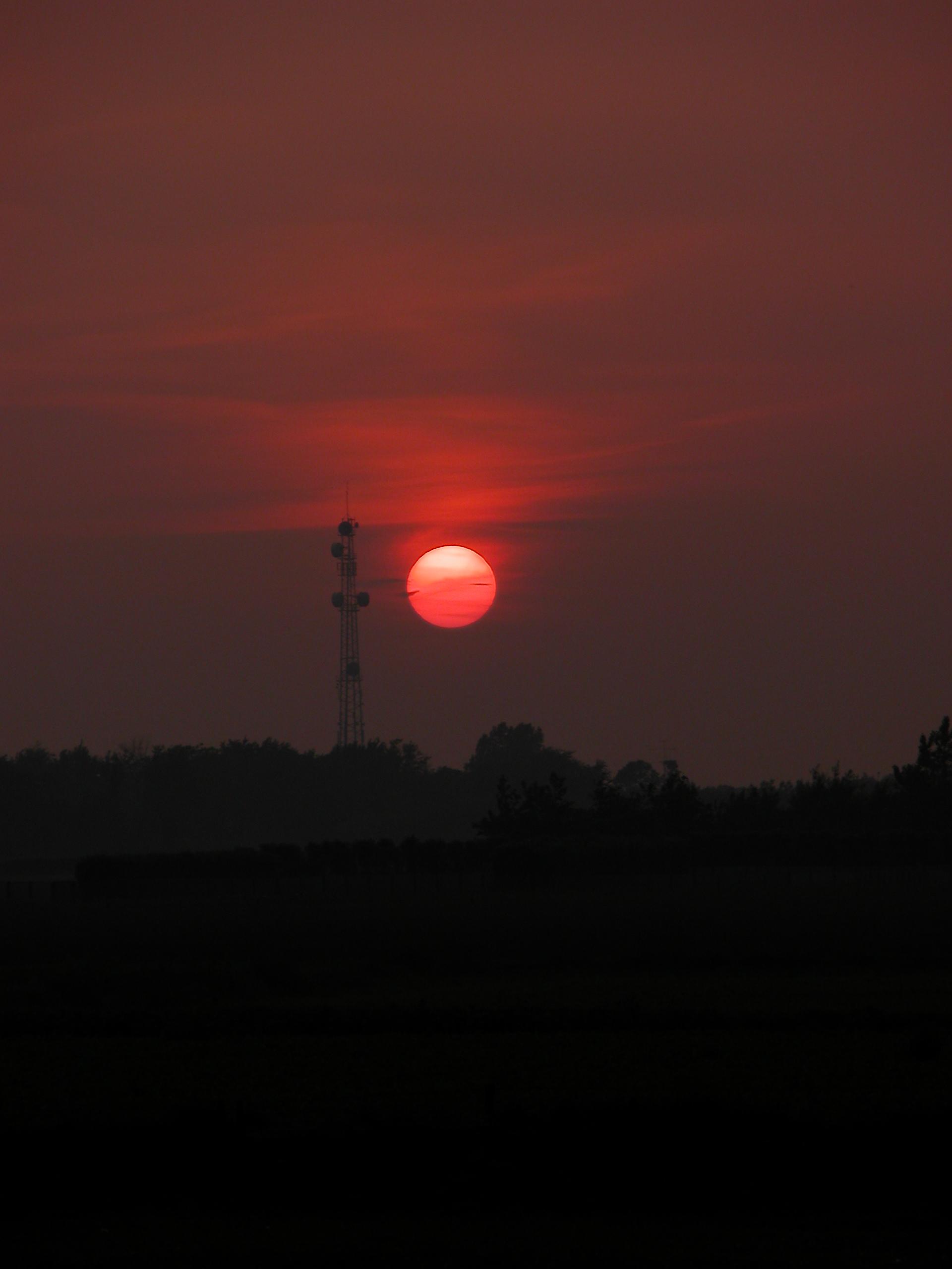 sunset red setting sun television mast broadcasting dark evening darkening