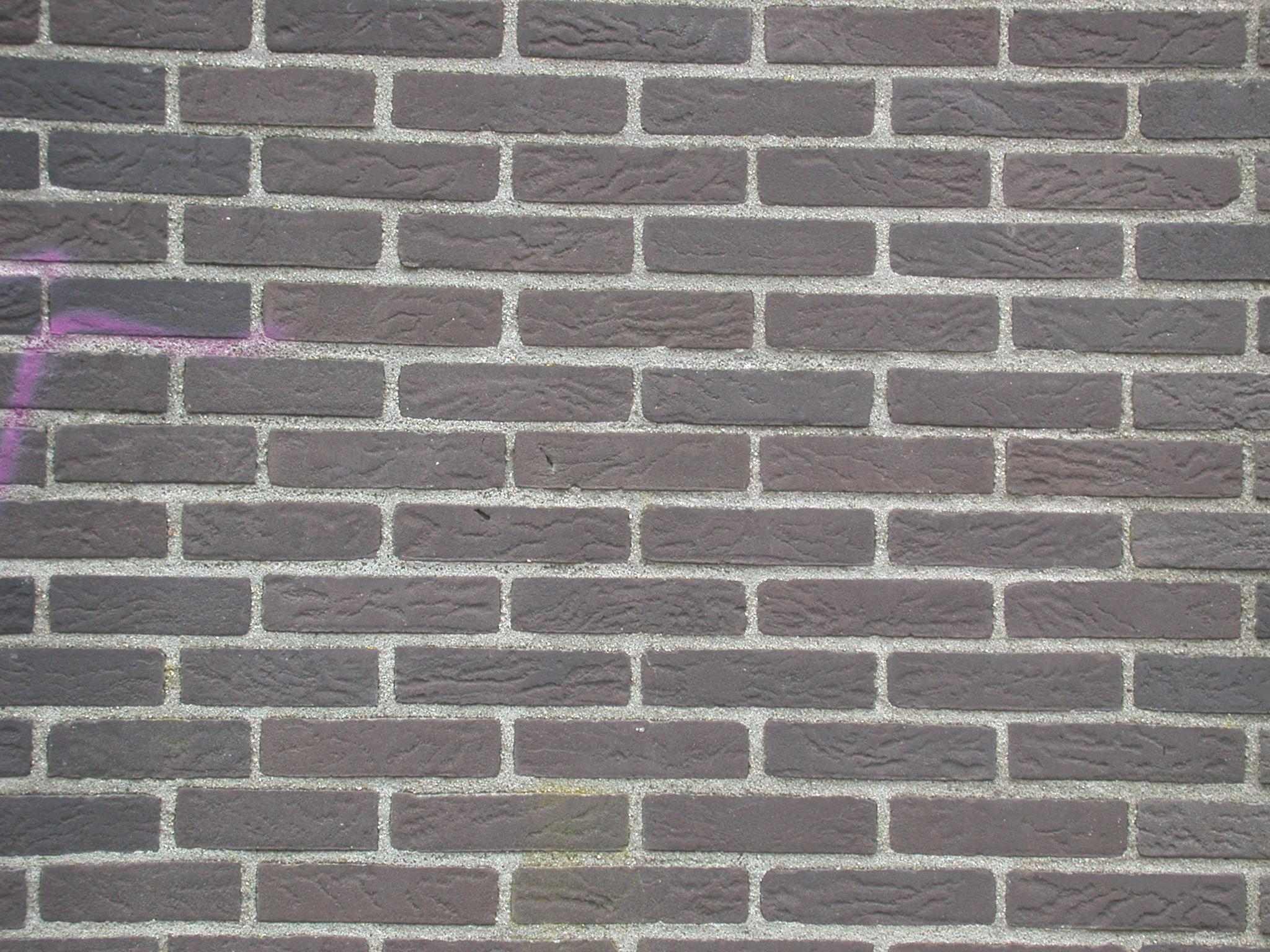 brown brick wall with some graffiti