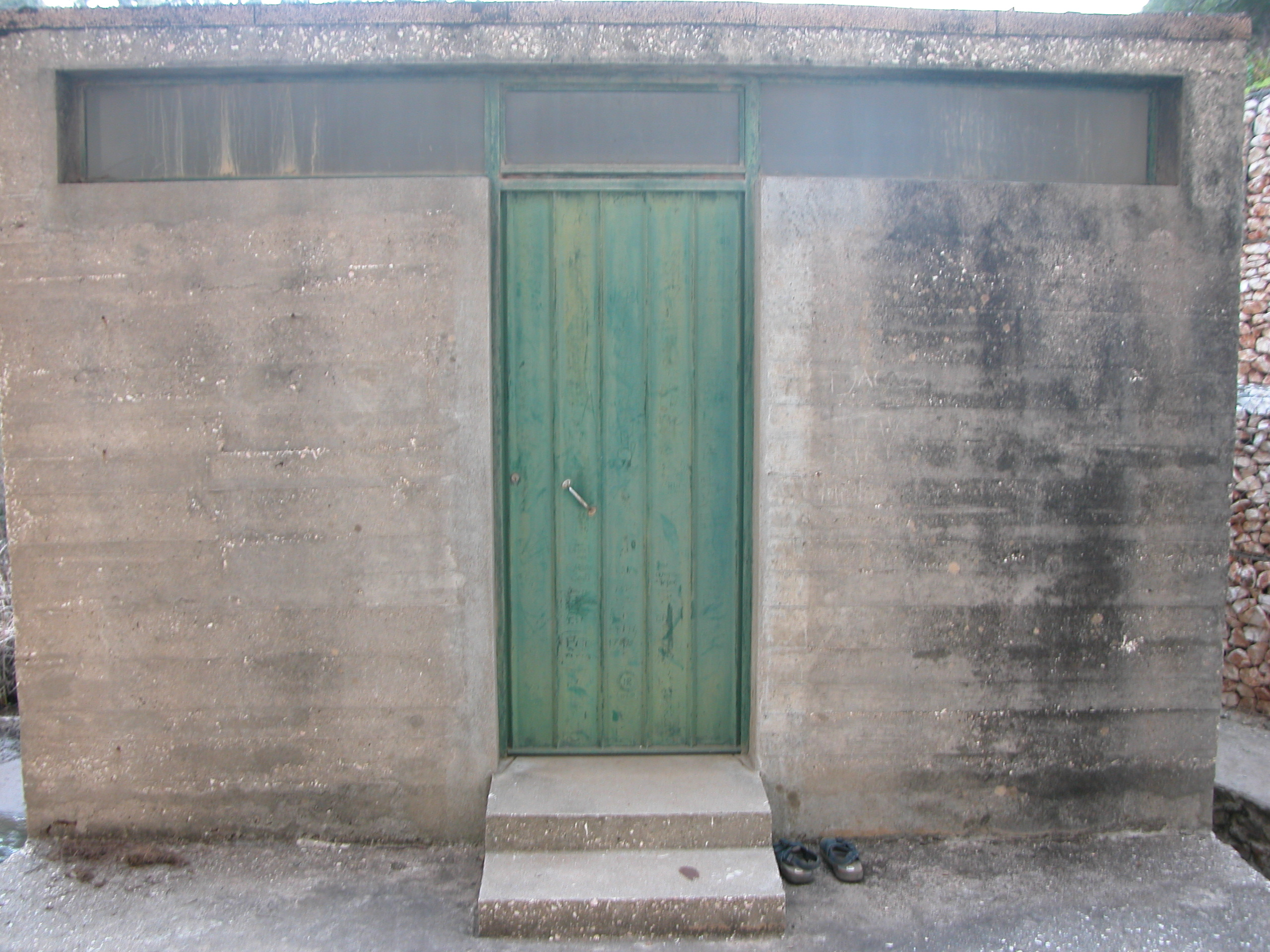wall hard cement stone door green wooden steps shed bunker