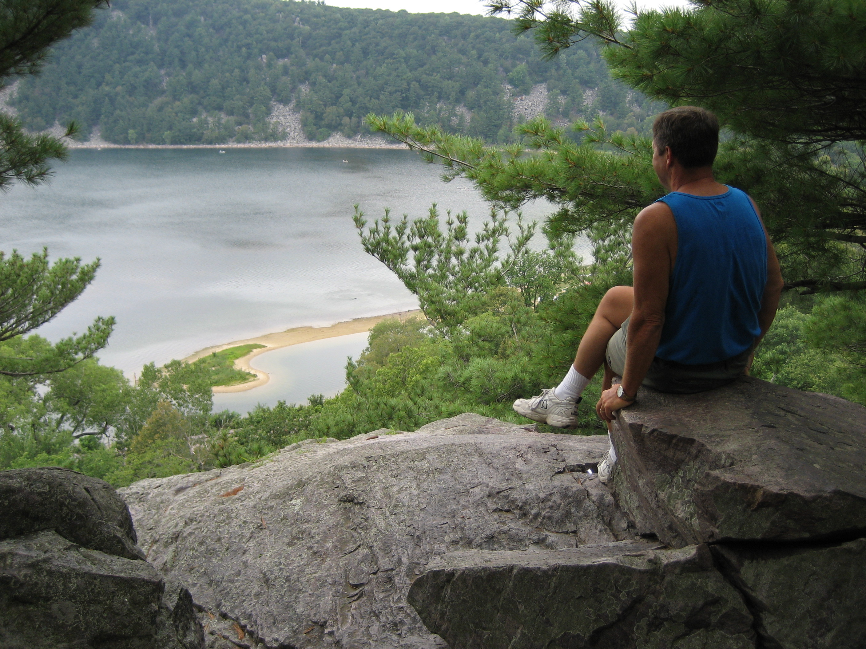 gallagher_lucas man looking over a lake trees rock sitting relaxing
