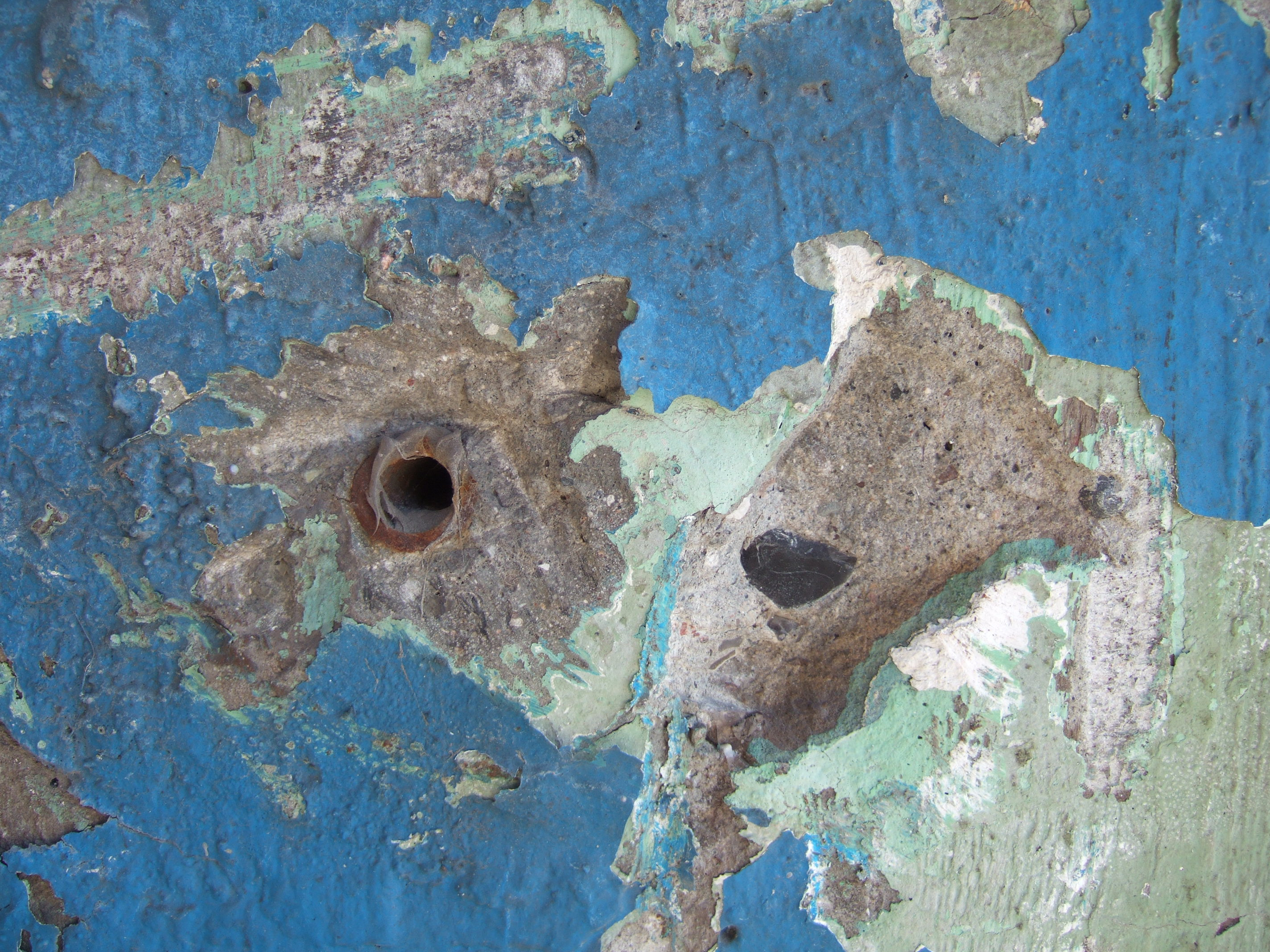 tabus hole in concrete pillar blue chipped paint corroded