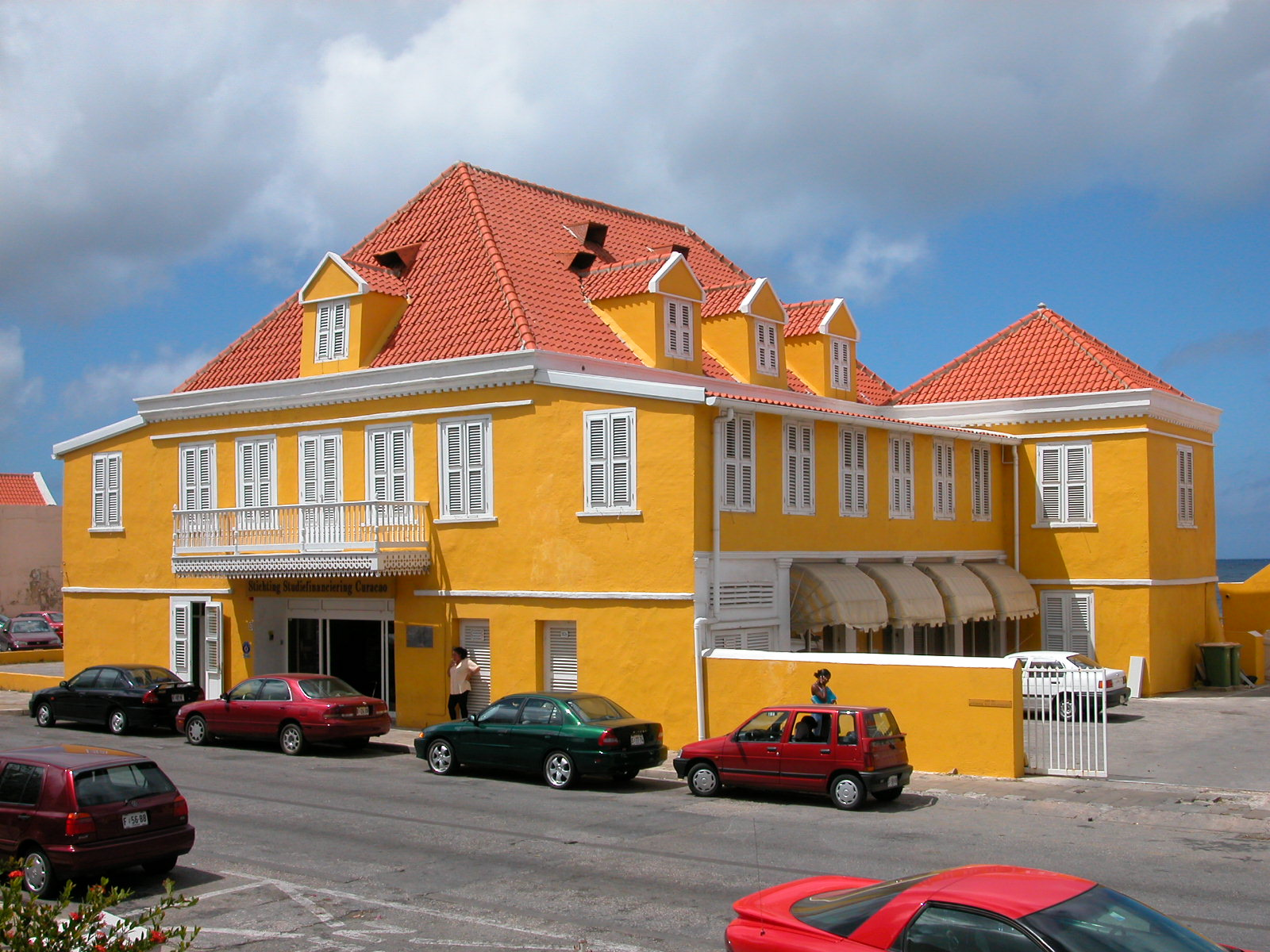 jacco curacao architecture exteriors building office stufi woman calling phone yellow cars parked