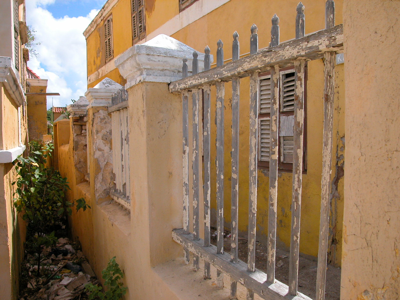 mediterrenean caribbean port fence gate yellow paint happy alley alleyway blinds shutters
