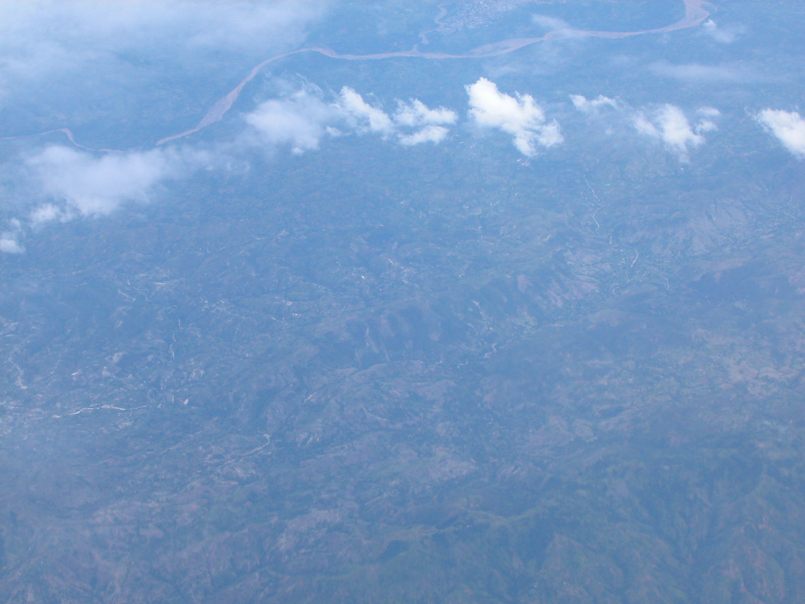 jacco sky view distance airoplane window blue clouds high altitude ground high up above the