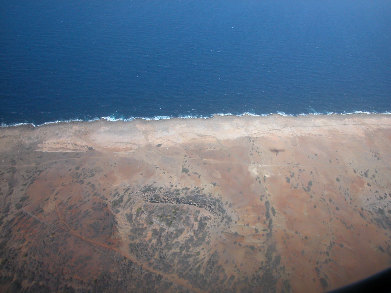 landscape from airplane aerial photo roads brown sea waves plane shadow